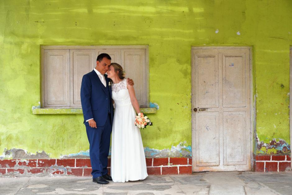 Bruidspaar bij een kleurige muur in Peru tijdens hun destination wedding in Zuid-Amerika. De fotograaf uit Nederland is meegereisd.