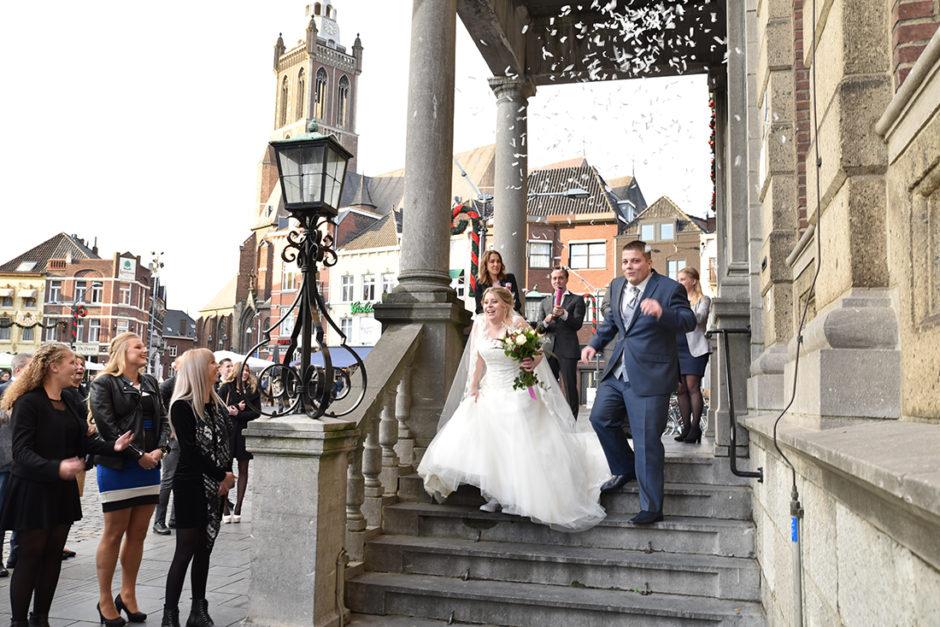 Bruidspaar rent van de trappen van het gemeentehuis in Roermond na de ceremonie.