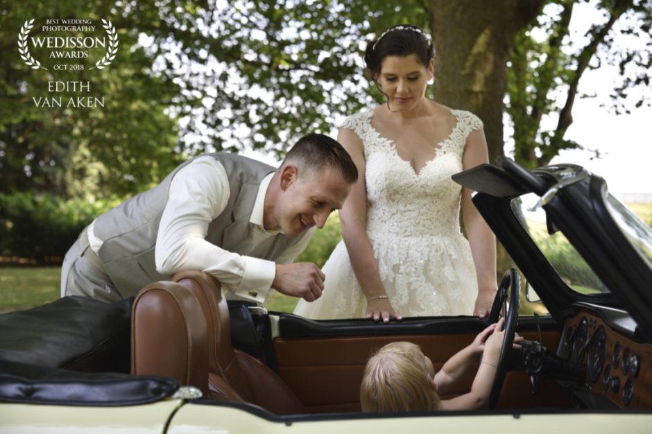 Award winnende foto van een bruidspaar bij de trouwauto met hun kindje aan het stuur.