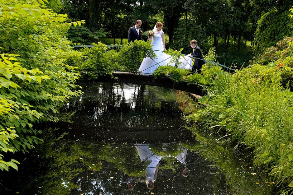 Bruidspaar op de brug in de tuinen van trouwlocatie kasteel Groot Buggenum in Grathem. De huwelijks ceremonie vond plaats in het kasteel en de trouwreportage in het kasteel en de tuinen.