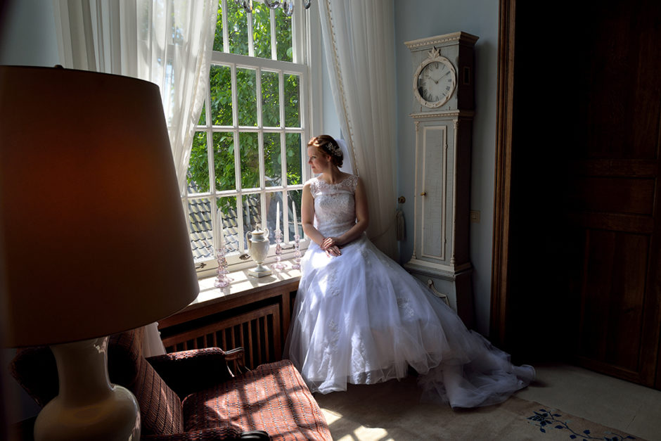 Klassieke bruid op de vensterbank bij het mooie raam van kasteel Groot Buggenum in Grathem, waar de trouw ceremonie ook heeft plaatsgevonden.