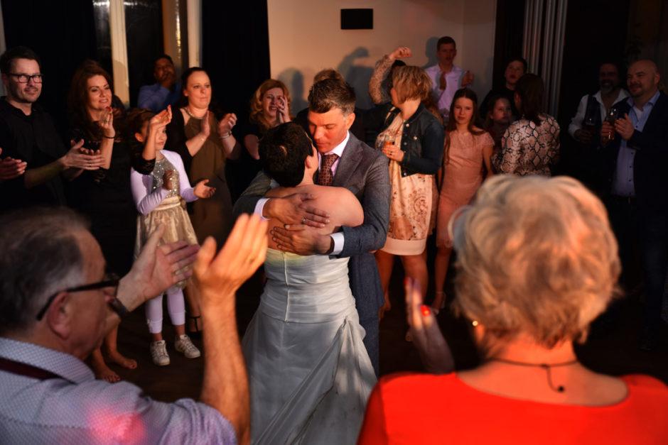 Bruidspaar tijdens de openingsdans tussen hun familie en gasten op landgoed Rhederoord in de Veluwe.