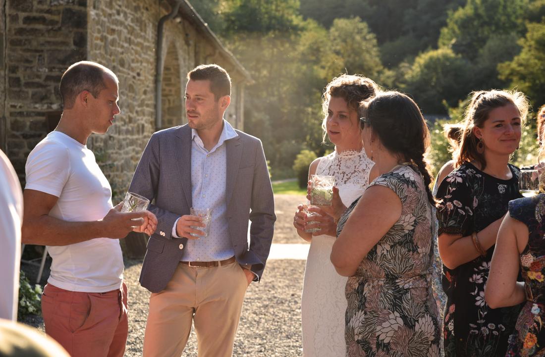 Sfeerfoto van het borreluurtje op een feest in de buitenlucht, da gasten zijn aan het praten.