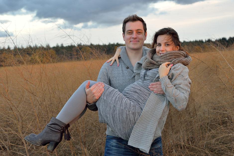 Foto van trotse aanstaande ouders tijdens een zwangerschapsshoot fotoshoot in de herfst of winter in de natuur nabij Roermond, midden-Limburg. Spontane Zwangerschapsfoto door familiefotografe.