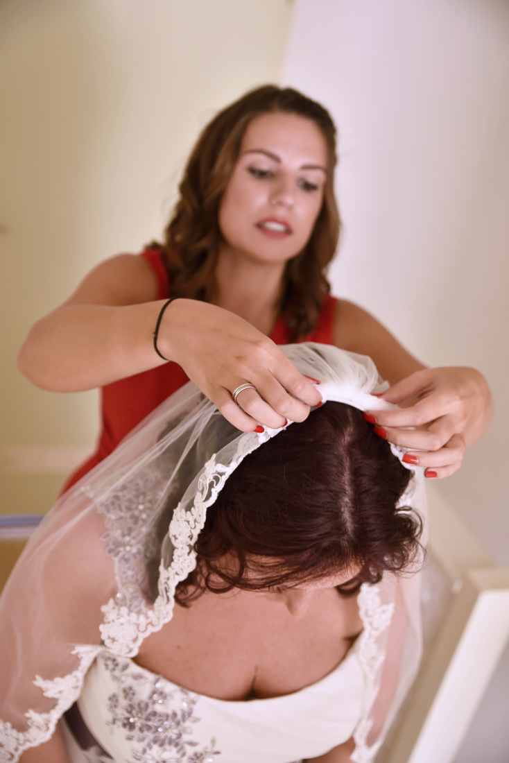 bridemaid is helping with the veil.