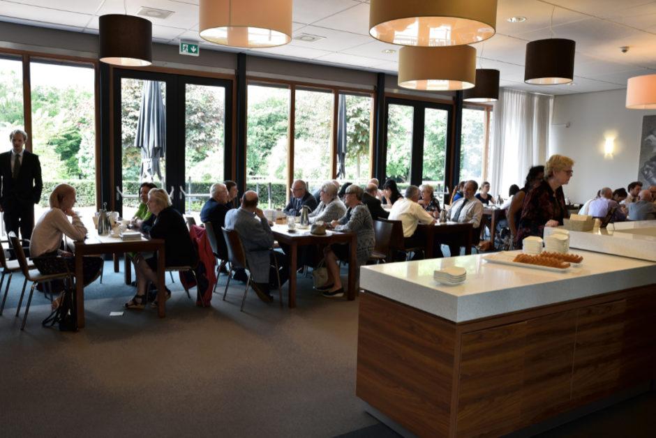 Een overzicht van de koffieruimte met alle mensen die naar een uitvaart zijn gekomen om de nabestaanden steun te betuigen in Roermond. Uitvaartfotografie in Roermond.