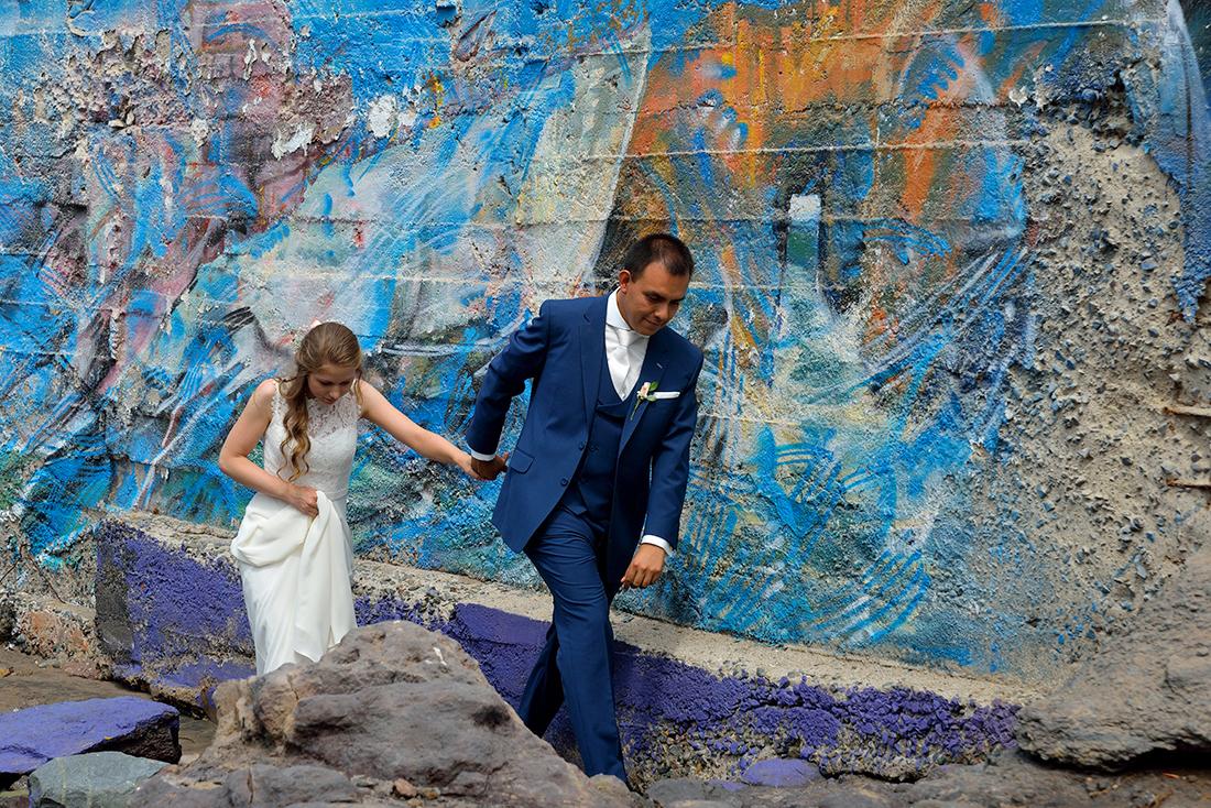 Stoere foto van een bruidspaar bij een muur met graffiti dat trouwde in het buitenland.
