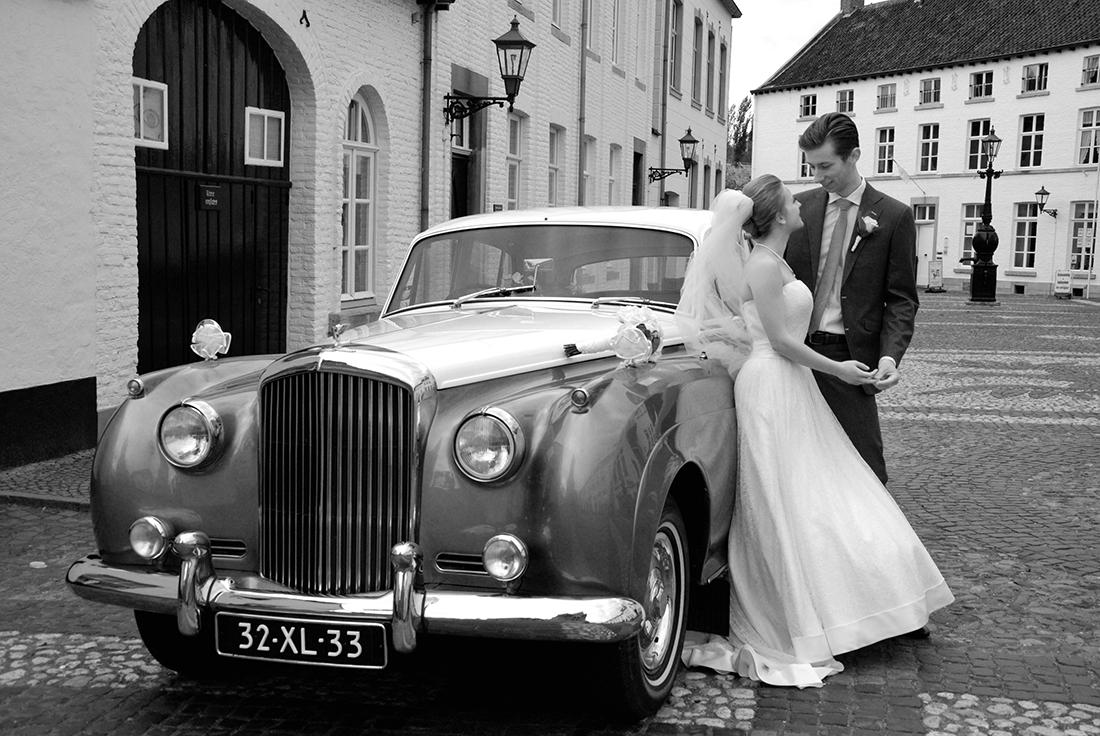 Bruidspaar bij hun trouwauto op hun trouwdag in Thorn