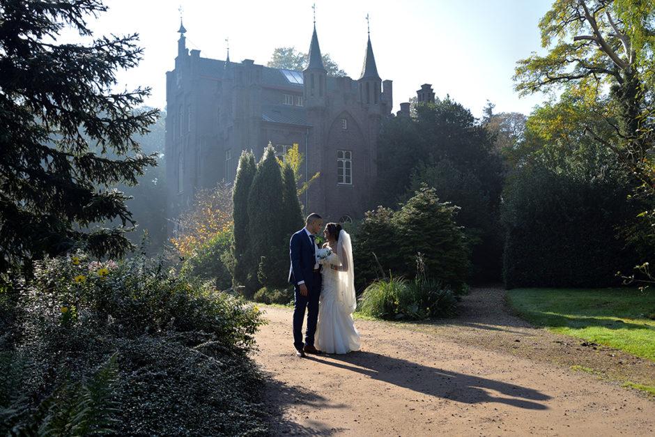 Bruidspaar tijdens de bruidsreportage met kasteel aerwinkel in de achtergrond tijdens de trouwdag van dit stel dat trouwde in Roermond.