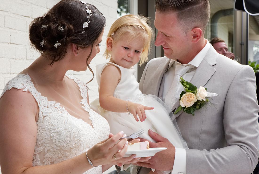 Bruidspaar en hun dochtertje nemen een hapje van de bruidstaart bij de trouwlocatie in Herten.