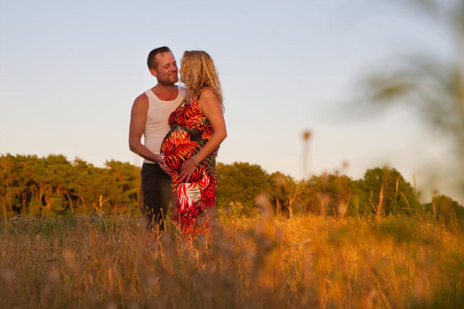 Zwangere vrouw en haar partner tijdens een fotoshoot in de natuur in midden-Limburg, vlakbij Roermond.