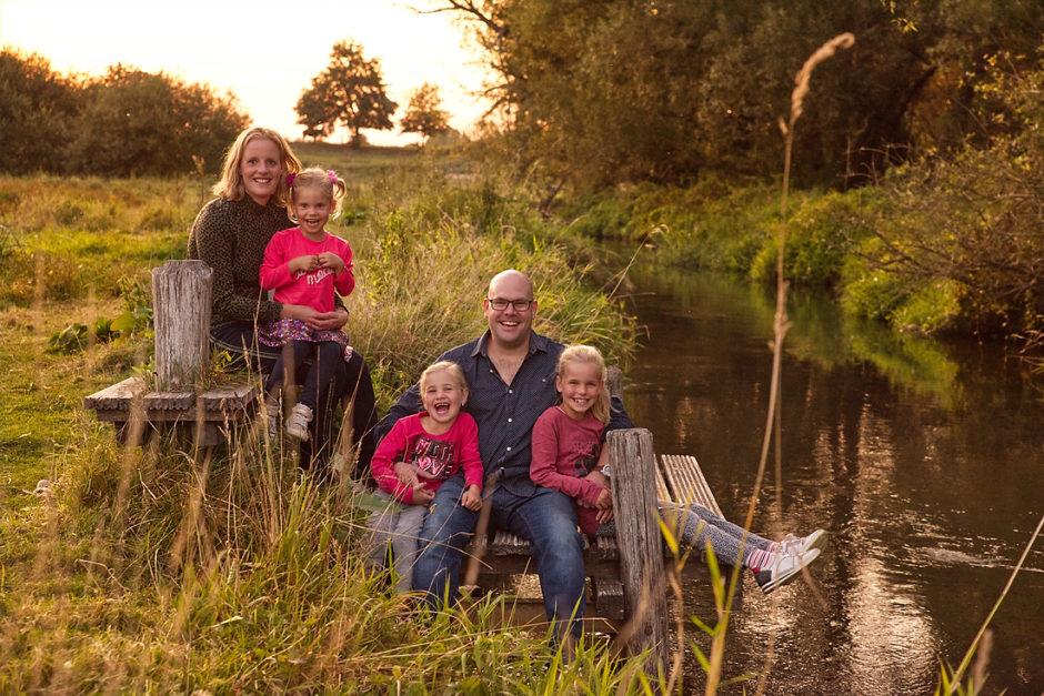 Een vrolijke foto van een gezin tijdens hun foto reportage in Roermond aan het water, vastgelegd door een fotografe uit Limburg.