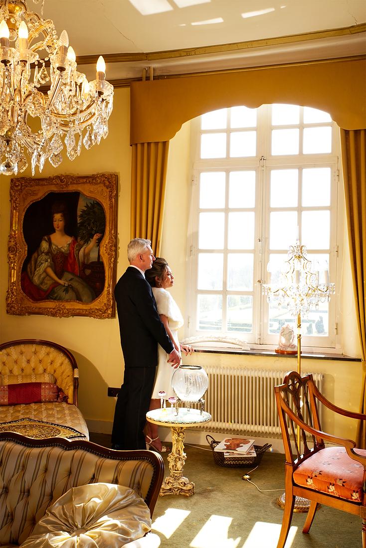 Bruidspaar bij een raam in kasteel Aldenghoor te Healen, vlakbij Roermond. In de 'gele kamer' staan prachtige meubels en de kroonluchter en mooie kunst zorgen voor een prachtige foto-locatie.
